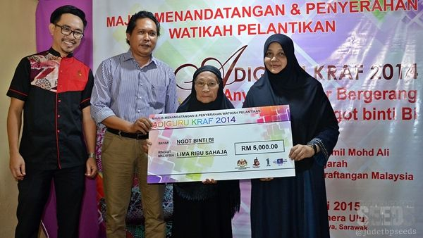 Malaysian Craft Preservation Department director Ruslah Khalid (right) handing over a cheque of cash prize totalling RM5,000 to the newly appointed Adiguru Kraf Ngot Bi (second right) in the presence of Sadong Jaya assemblyman Aidel Lariwoo (second left) and State Malaysia Handicraft Development Corporation director Azran Arip.