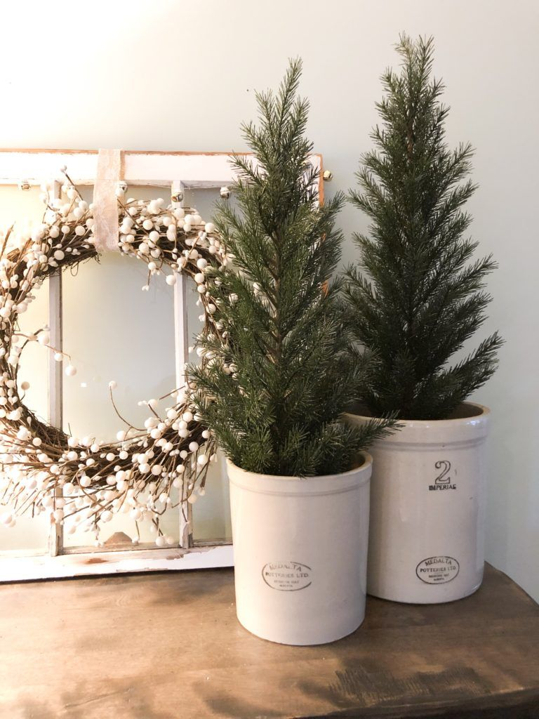 Transition your Christmas decor to winter decor by using evergreen trees in crocks for the winter. A Winter Mantel & Living Room Decor – Valley + Birch #winterdecor #winterdecorating #farmhousestyle #vintagedecor #winterdecor