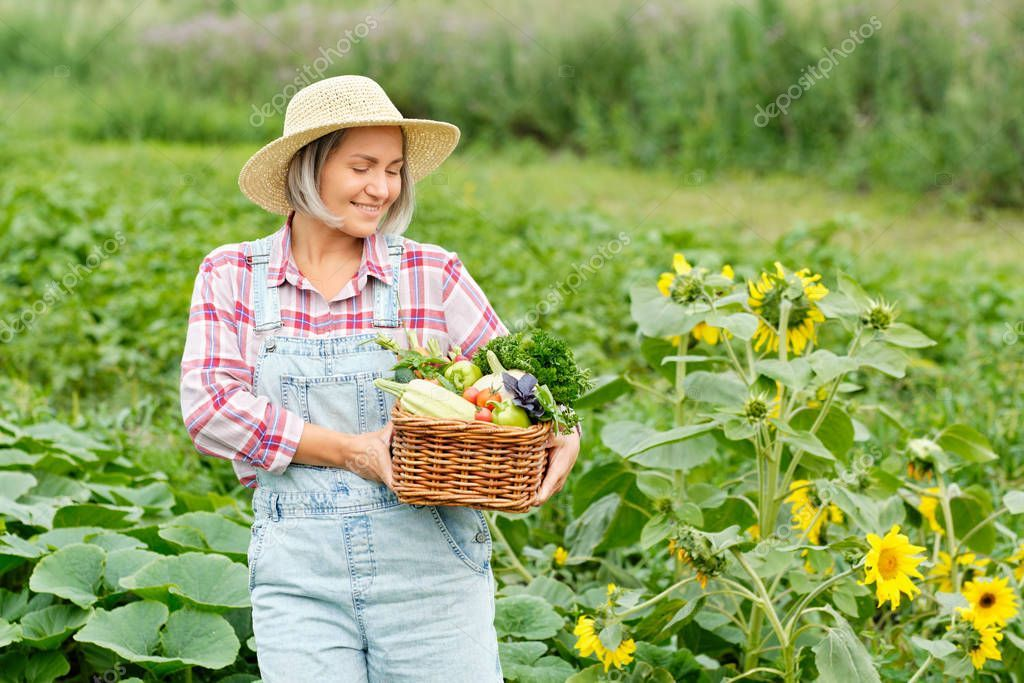 Woman Holding a Basket full of Harvest Organic Vegetables
