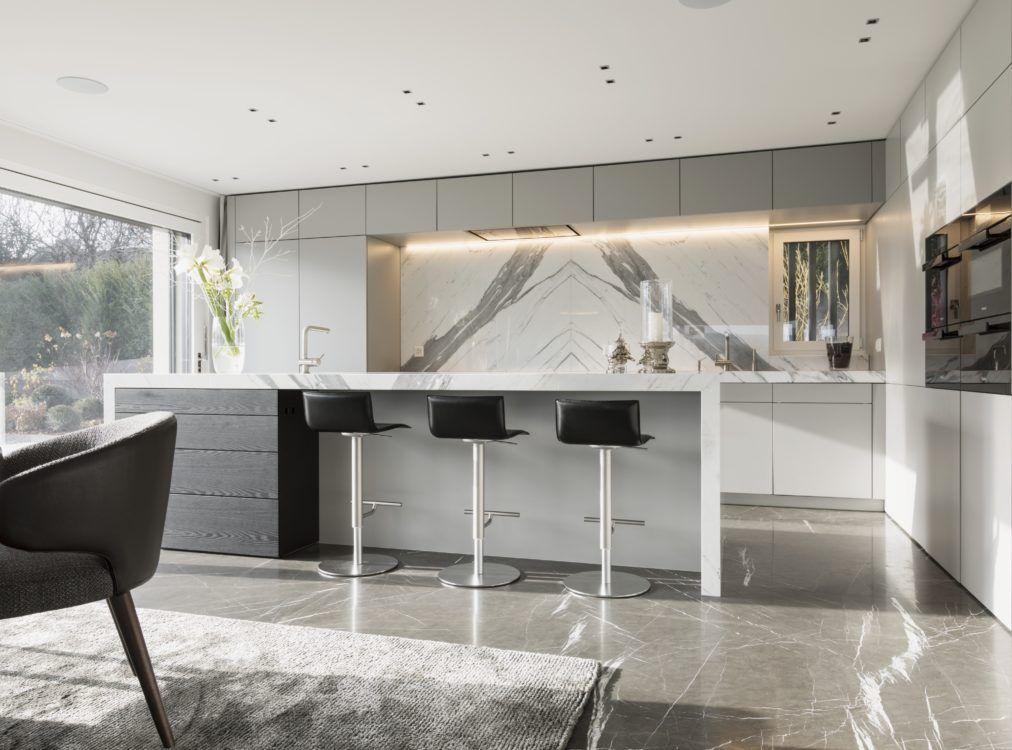 Die kochinsel der luxus küche bildet den gewünschten kontrast zu dem dunkleren naturstein boden