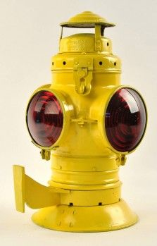 """Bell bottom caboose marker lamp manufactured by Armspear with last patent date of 1915, painted brilliant yellow color with amber and red lenses. Mounting bracket is attached, however no pot or burner inside. size: 14.5"""" t."""