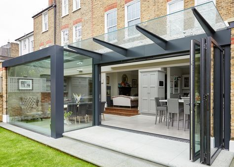A rear replacement extension to form an open plan kitchen and dining space incorporating a glass roof, bifold doors and and canopy