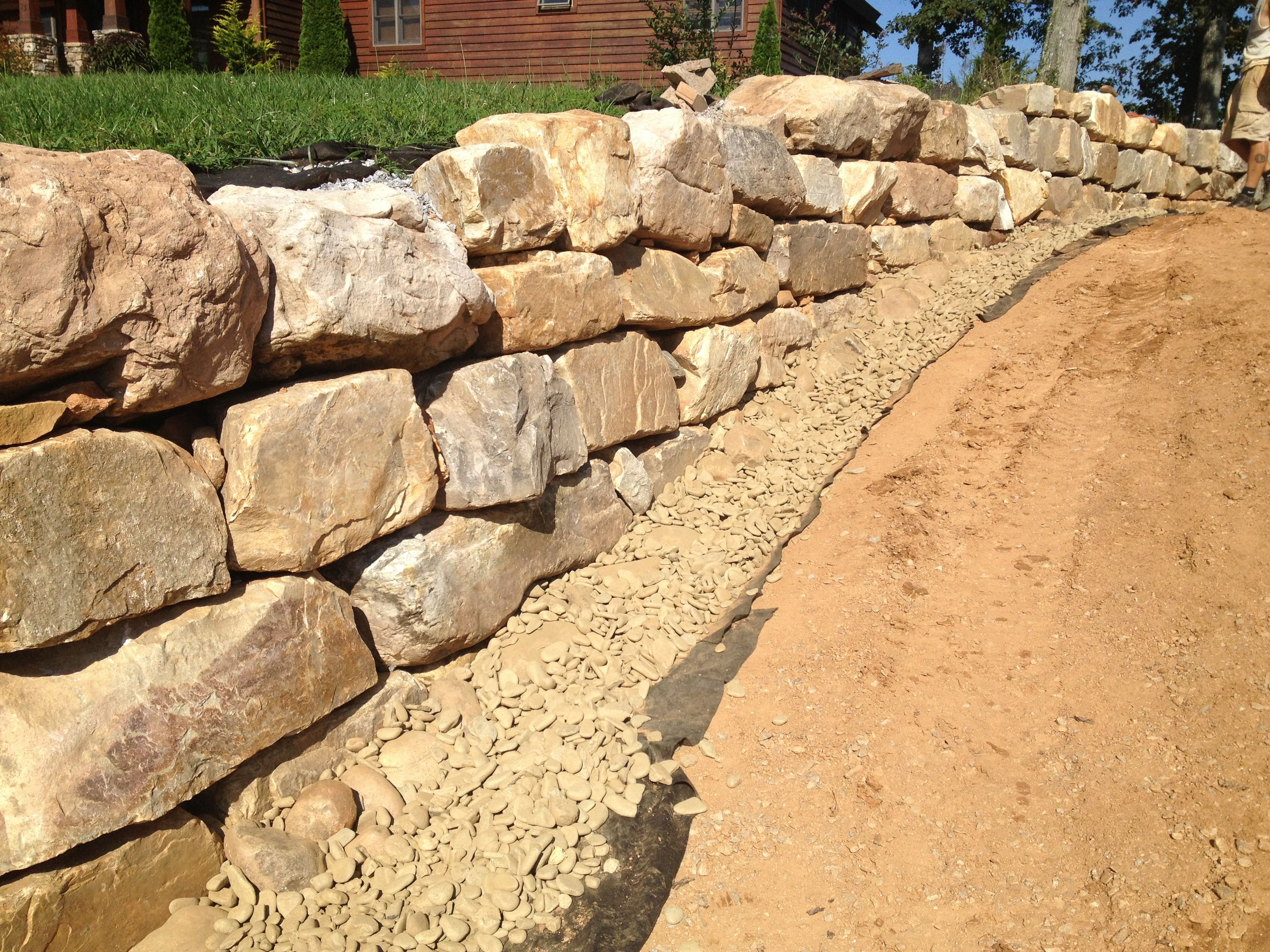 Boulder wall with river gravel installed at the base to facilitate ...