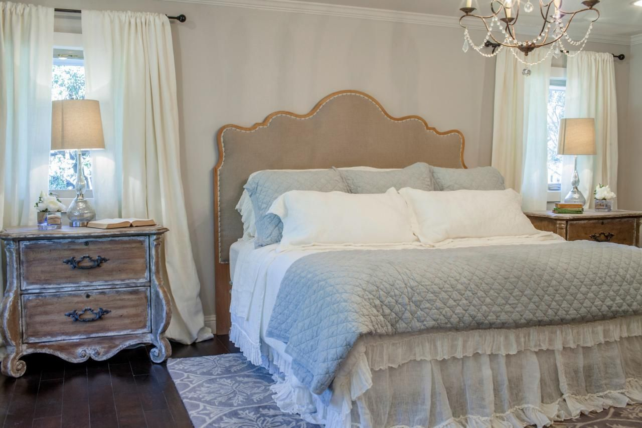 fixer upper midcentury upholstered headboard dust ruffle ornate side tables and chandelier with draped crystal all combine to give the master suite a feminine and romantic