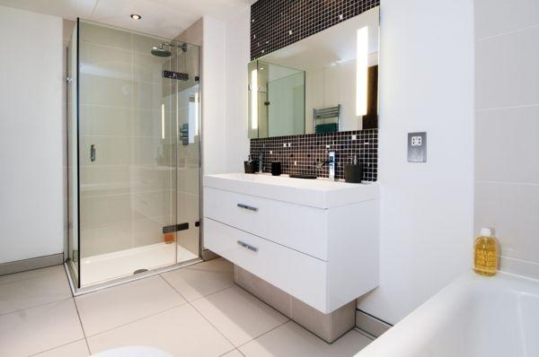 vasque rectangulaire, un carrelage mosaique noir, un miroir mural rectangulaire et un sous vasque blanc