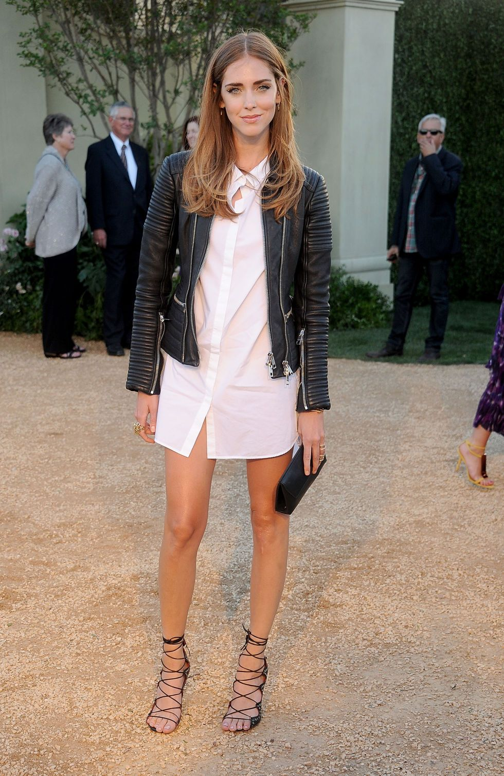 White shirt dress with a leather moto and strappy heels.