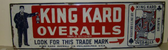 Large sign for King Kard Overalls showing a playing card to the right of the sign and to the left is a gentlemen holding a lantern wearing the company's overalls.