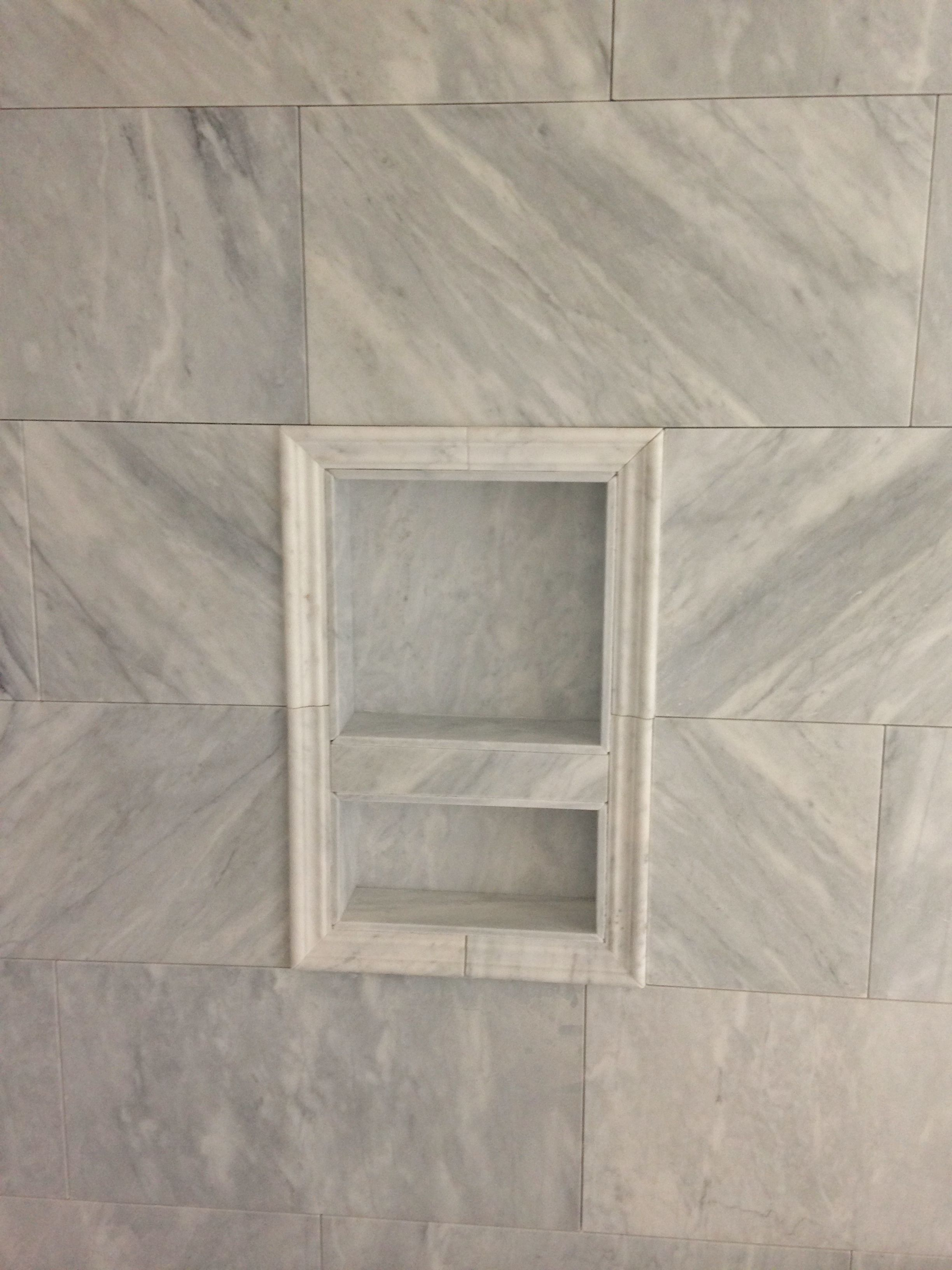 Carrara marble at Master shower walls with niche framed in Carrara
