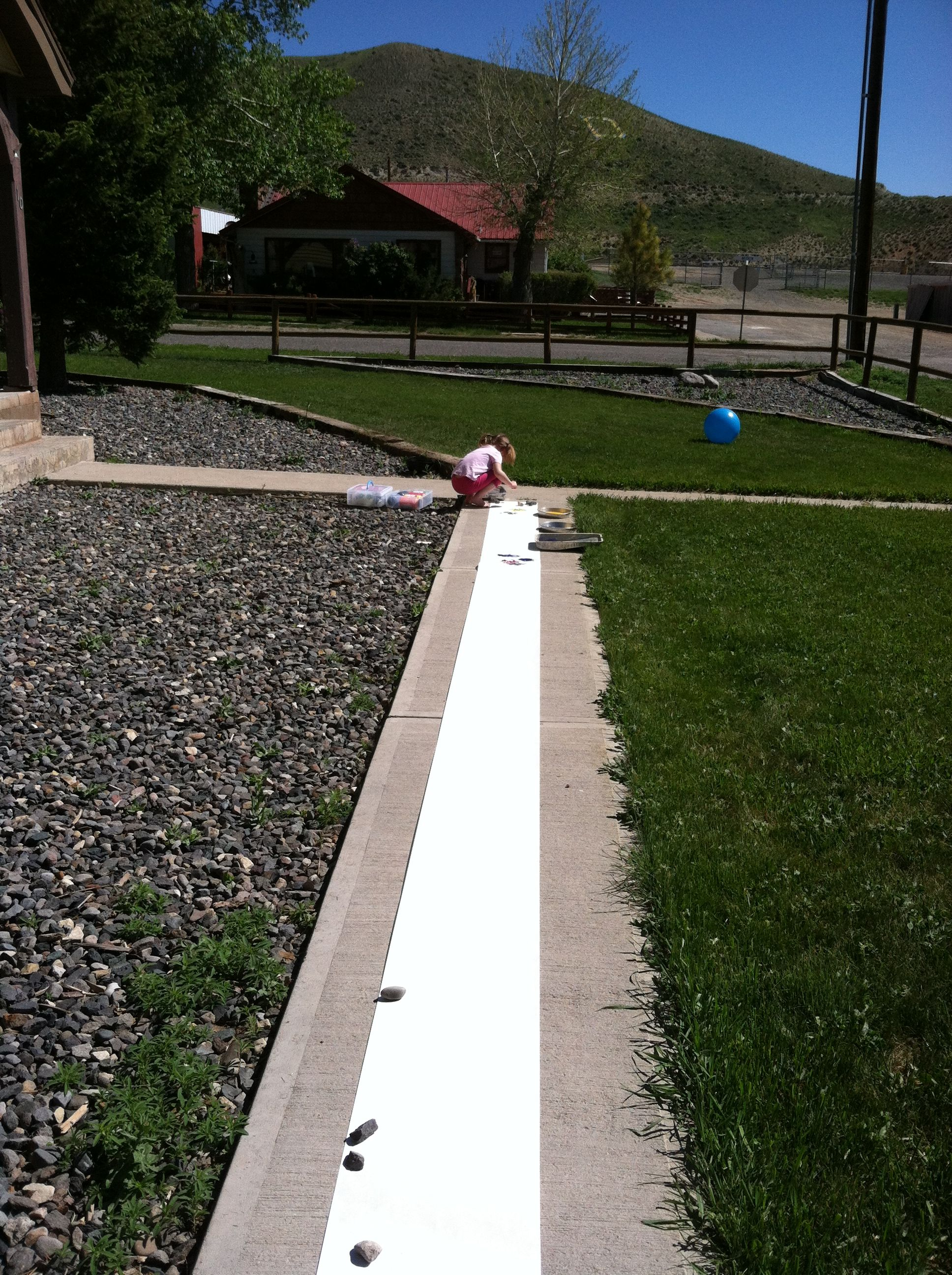 Using a roll of craft paper, line the sidewalk with paper.
