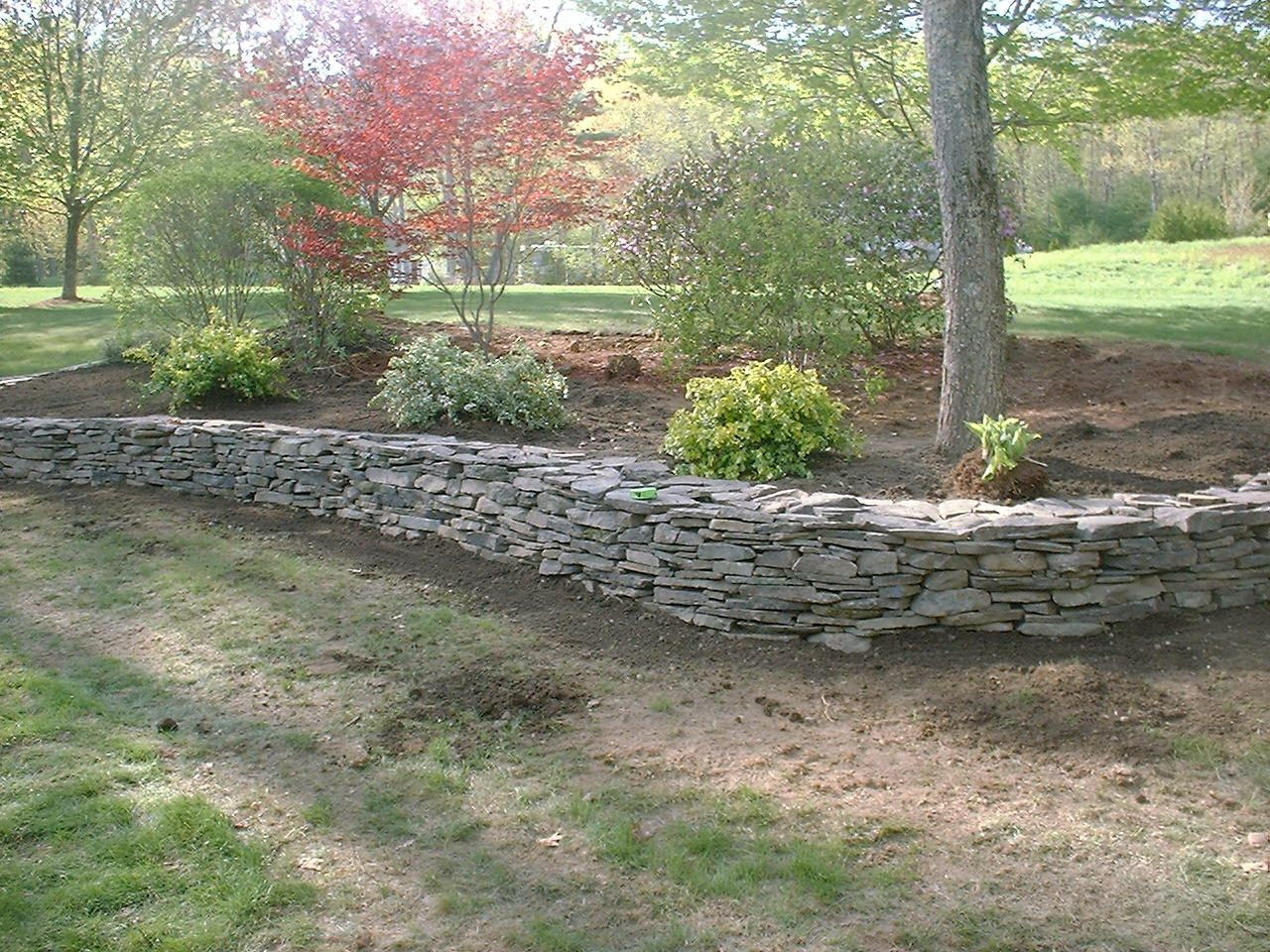 Stone retaining walls natural stone retaining wall and for Rock garden bed ideas