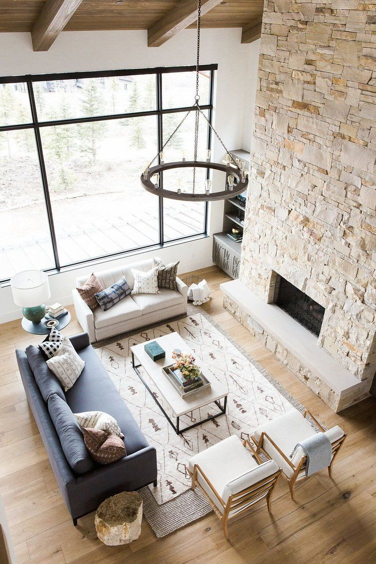 Photo of Great room with dramatic stone fireplace, layered rugs, and neutral color scheme…