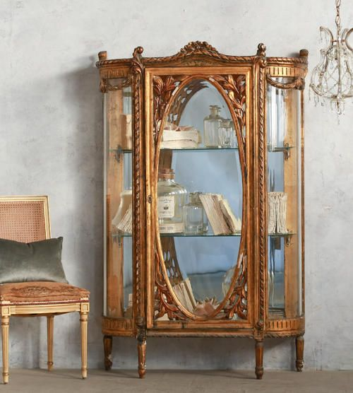 ELOQUENCE® www.eloquenceinc.com Absolutely stunning vintage vitrine in aged chipping gilt finish with original bevelled curving glass sides and oval glass door. Mirrored interior with glass shelves. Ornate carved olive leaf detailing around door frame. So rare to find pieces like this! 66H x 43W x 16D Circa: 1930
