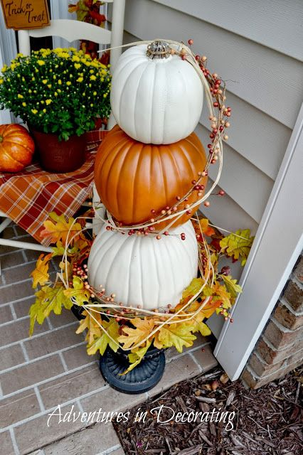 Adventures in Decorating: Fall Front Porch. Great for autumn, fall, or thanksgiving decor. White and orange stacked pumpkins with beige grass and red cranberry sticks wrapped around like a tower on a vase. Red, yellow, orange, and green Leaves scattered at the base.