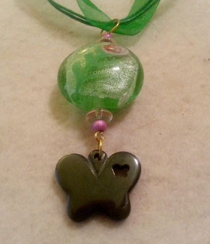 """**Green glass flower bead with butterfly charm pendant. This pendant is made with this gorgeous green glass bead with a flower that I have paired with light pink rondelles and small pink stardust beads. It has been finished with a black hemalyke butterfly. It is strung on an 18"""" green organza necklace."""