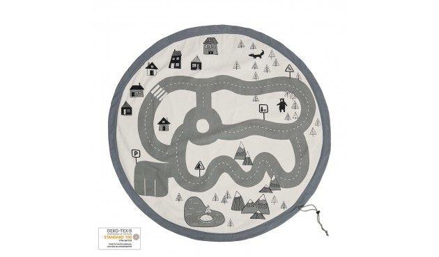 Die graue Aufbewahrungstasche aus dem Hause Bloomingville kombiniert Spiel, Spaß und Praktikabilität und macht damit kleine und große Menschen gleichermaßen glücklich. Wird die Tasche ausgerollt, verwandelt sie sich in einen kinderfreundlichen Spielteppich mit einem Durchmesser von 130 cm, der mit einer wunderschönen Landschaft aus Straßen, Bergen, Häusern und Tieren bedruckt ist. Darauf lässt es sich herrlich mit kleinen Spielzeugautos herumdüsen oder mit Püppchen spielen. Abwechslung bietet die Rückseite mit kleinem Pfeilmotiv, die zu weiteren Spielen einlädt und der Langeweile keine Chance lässt. Und wenn das Spiel vorbei ist, wird der Teppich mit einem Zug an der praktischen Kordel wieder zur funktionalen Aufbewahrungstasche mit großem Beutel, in dem alle Spielsachen verschwinden.## Besonderheiten# – praktische Aufbewahrungstasche mit Wende-Spielteppich inklusive Zugband – Durchmesser: 130 cm – Bezug: 100% Baumwolle – waschbar – funktional und pflegeleicht