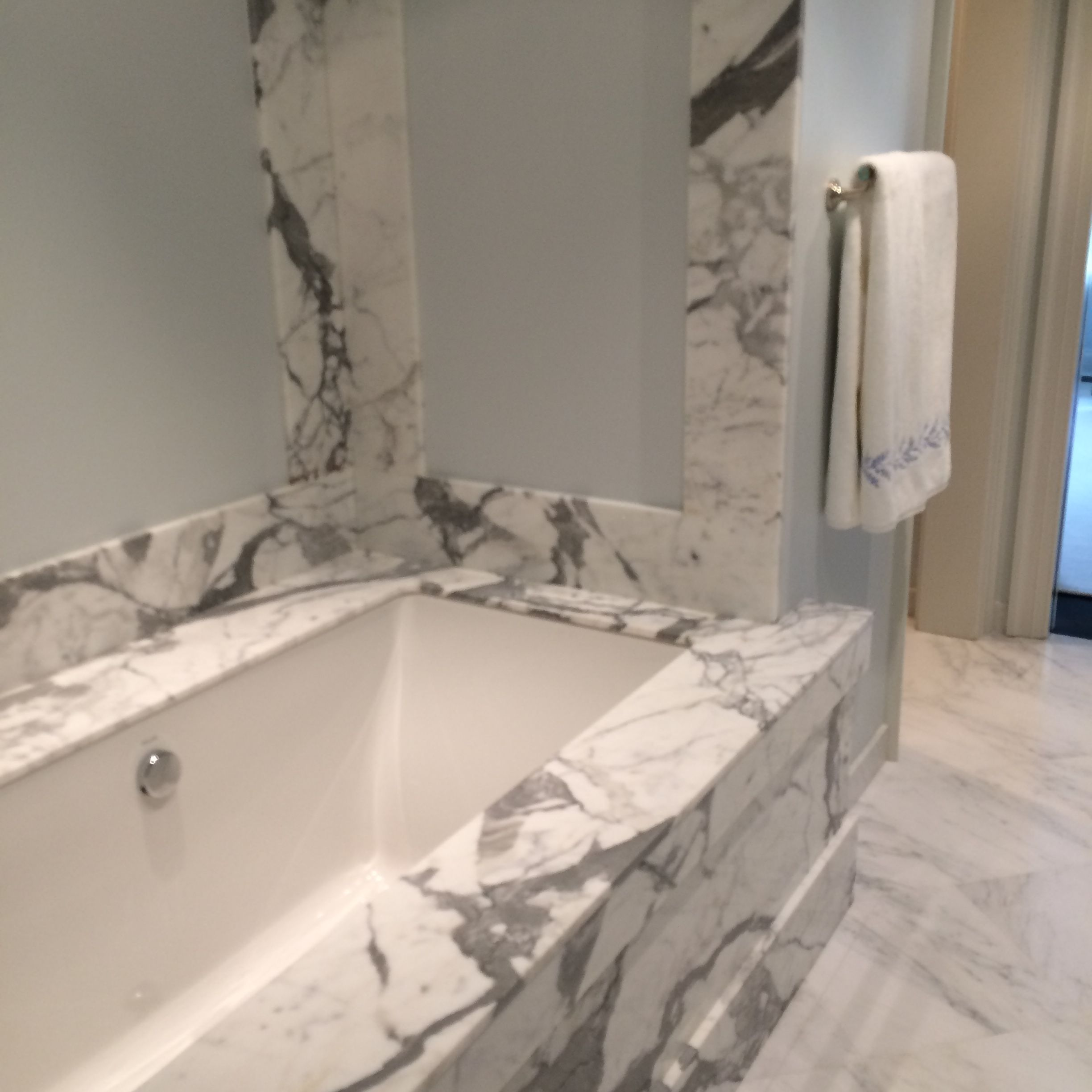 Undermount tub with marble deck, surround and paneled wall. mgpb.com ...