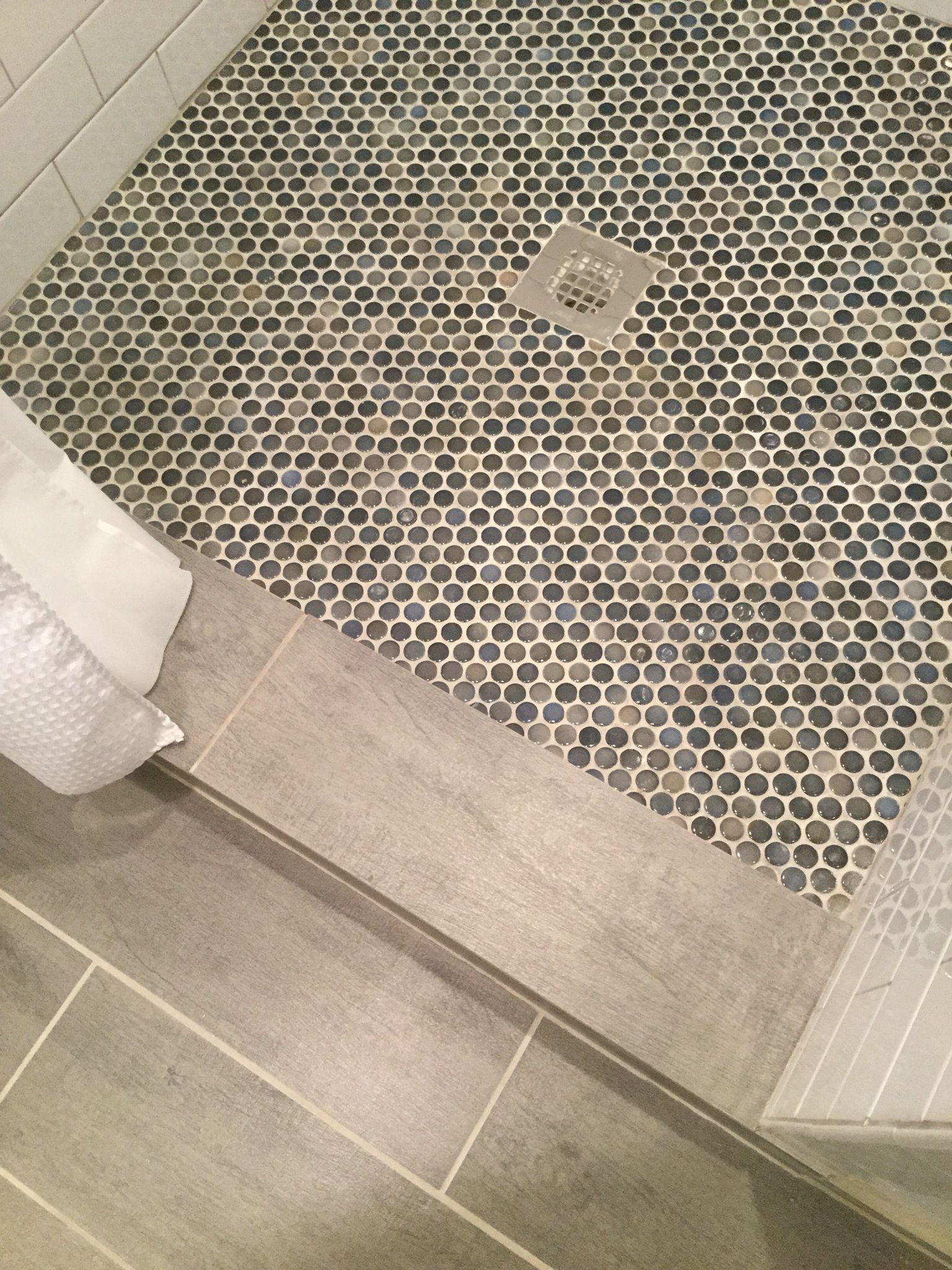 Blue and gray penny tile on shower floor.
