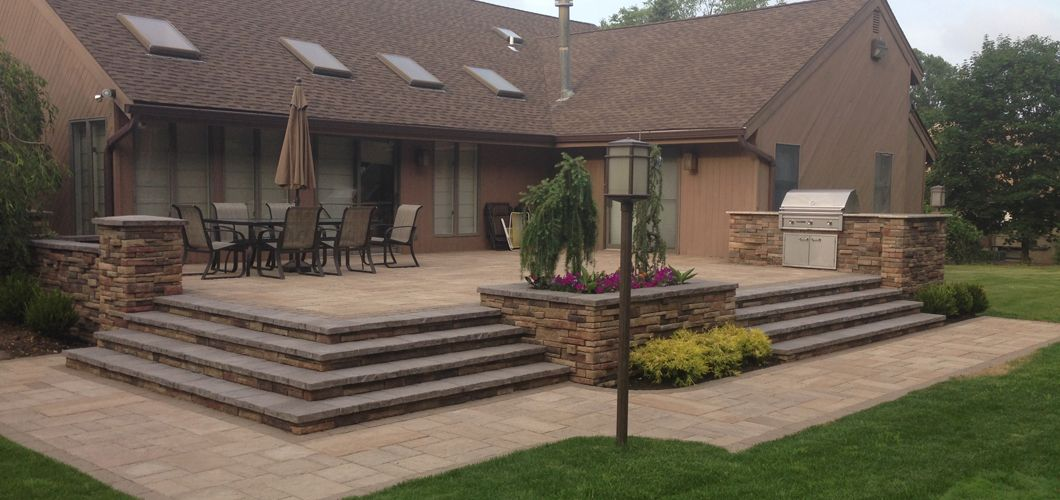 Elevated Patio With Built In Grill And Stone Countertops Built Using Kichlerstyle Lighting Techobloc Pavers And Patio Outdoor Kitchen Patio Built In Grill