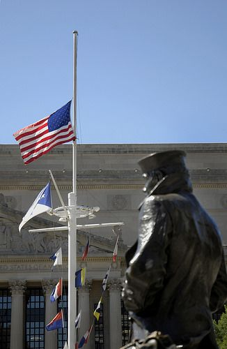 The Statue Of The Lone Sailor Looks Toward The American Flag As It Flies At Half Mast Navy Memorial American Flag American Flags Flying