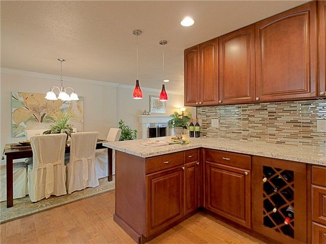 maple cognac wood kitchen cabinets with wood looking tile flooring ...