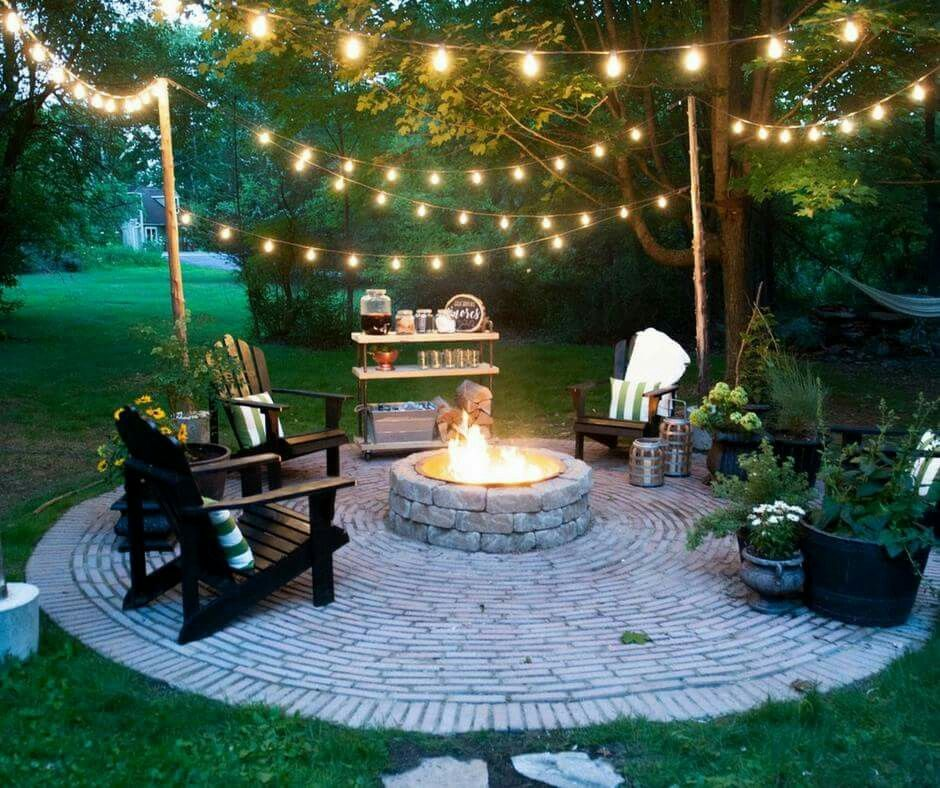 Beautiful backyard scene, with rope lights strung between movable poles stabilized in concrete. #backyardoasis