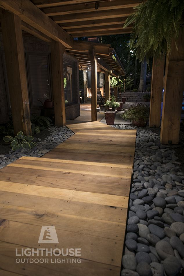 Recessed low voltage lighting tucked into the beam rafters of this deck illuminate the wooden