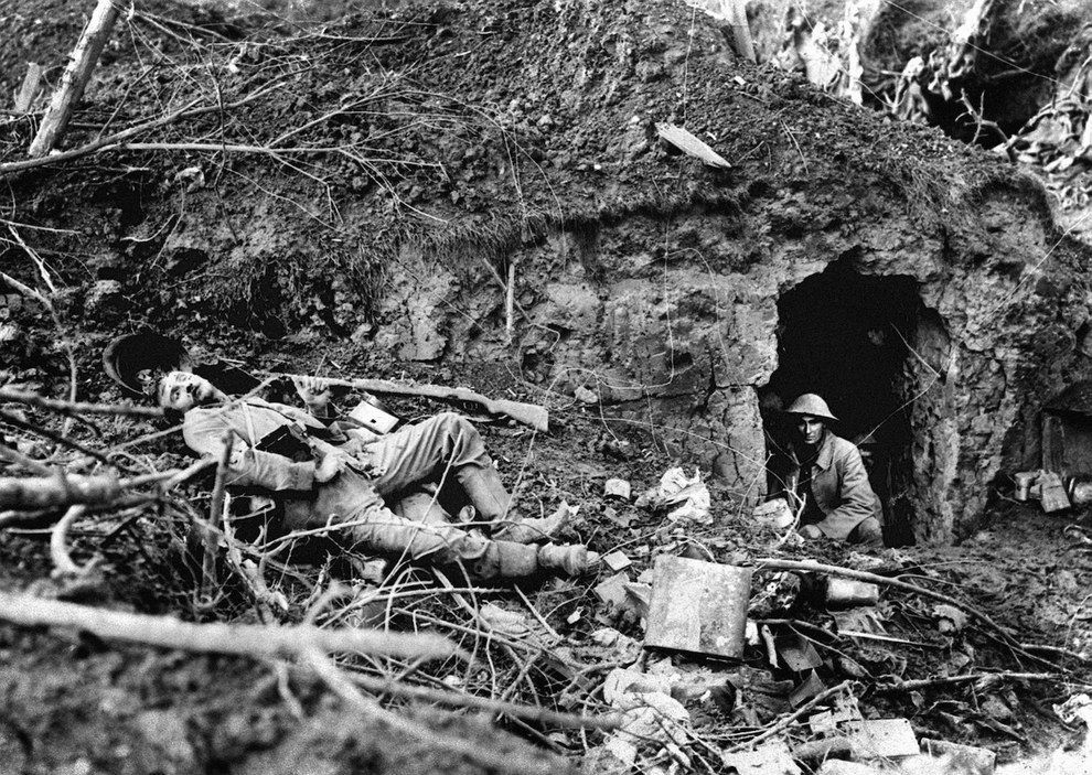 A British soldier gazes out of a dugout with the body of a dead German soldier nearby at Flers, during the battle of the Somme, 1916.