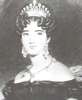 TThe original Lovers Knot Tiara designed in the mid-Georgian period in 1818, was given as a gift to Princess Augusta of Hesse-Cassel by her parents, Prince Frederick of Hesse and Princess Caroline of Nassau at the time of her marriage to Prince Adolphus, the Ist Duke of Cambridge, the 10th born child and the seventh son of King George III. In 1838, the Duchess of Cambridge wore the original Cambridge Lovers Knot Tiara for the coronation of Queen Victoria