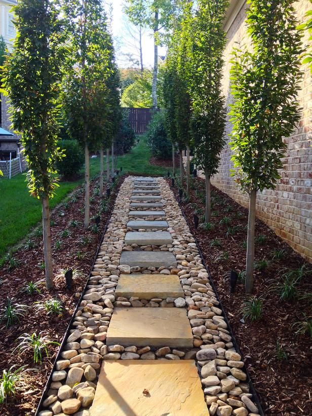 Square stepping stones set in large tumbled pebbles, and ...