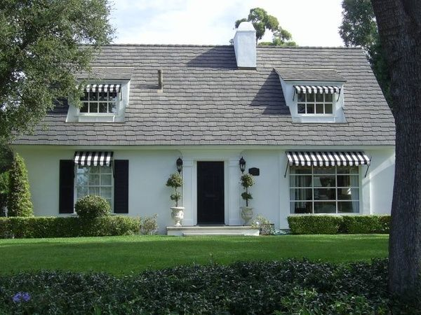 White Cottage Home With Black And White Awnings Boxwood Hedges And Topiaries Flanking The Fron White House Black Shutters House Exterior White Exterior Houses