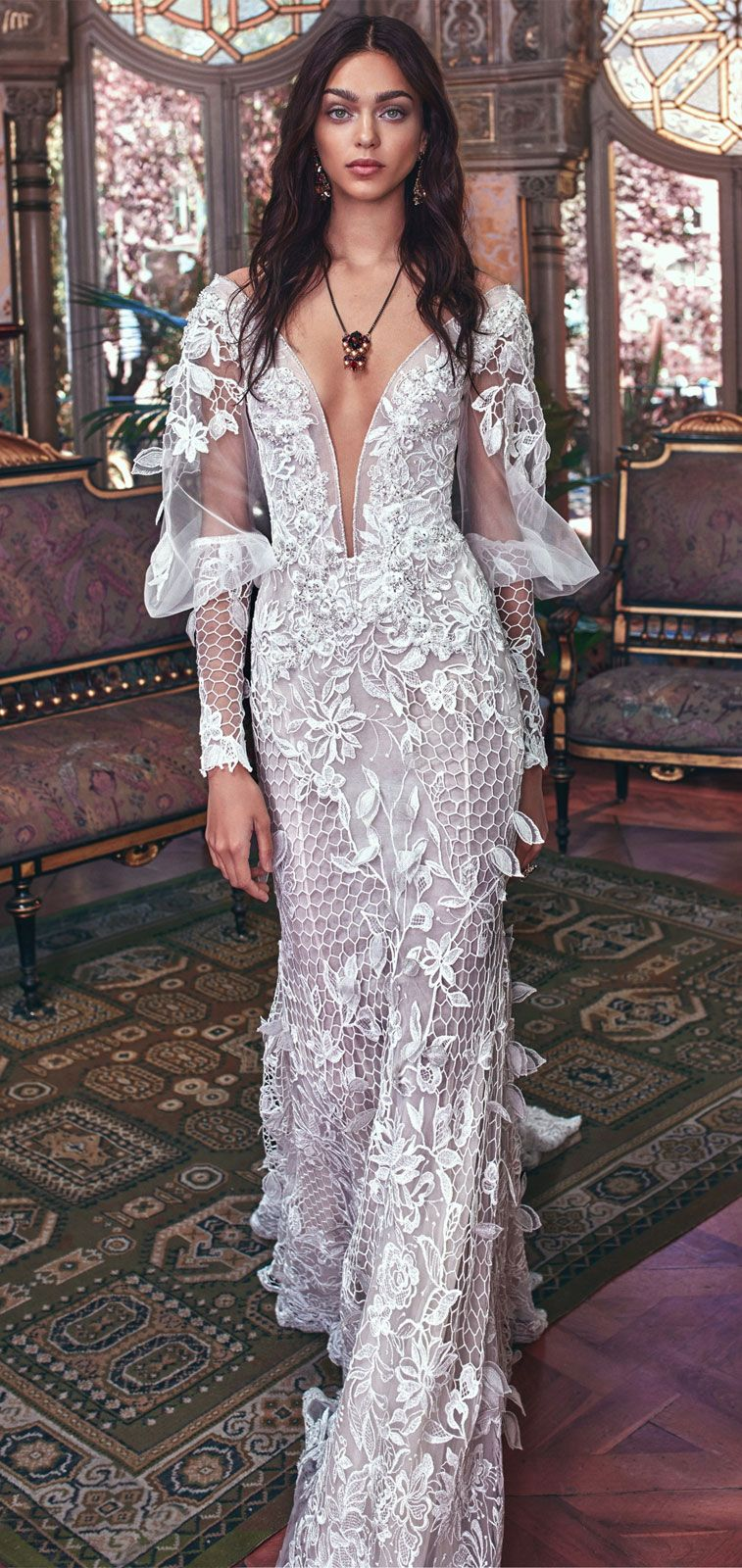 3D lace gown with open work fish net elements, a low plunging V neckline, and sheer Victorian sleeves with lace cuffs #wedding #weddingdress #weddinggowns
