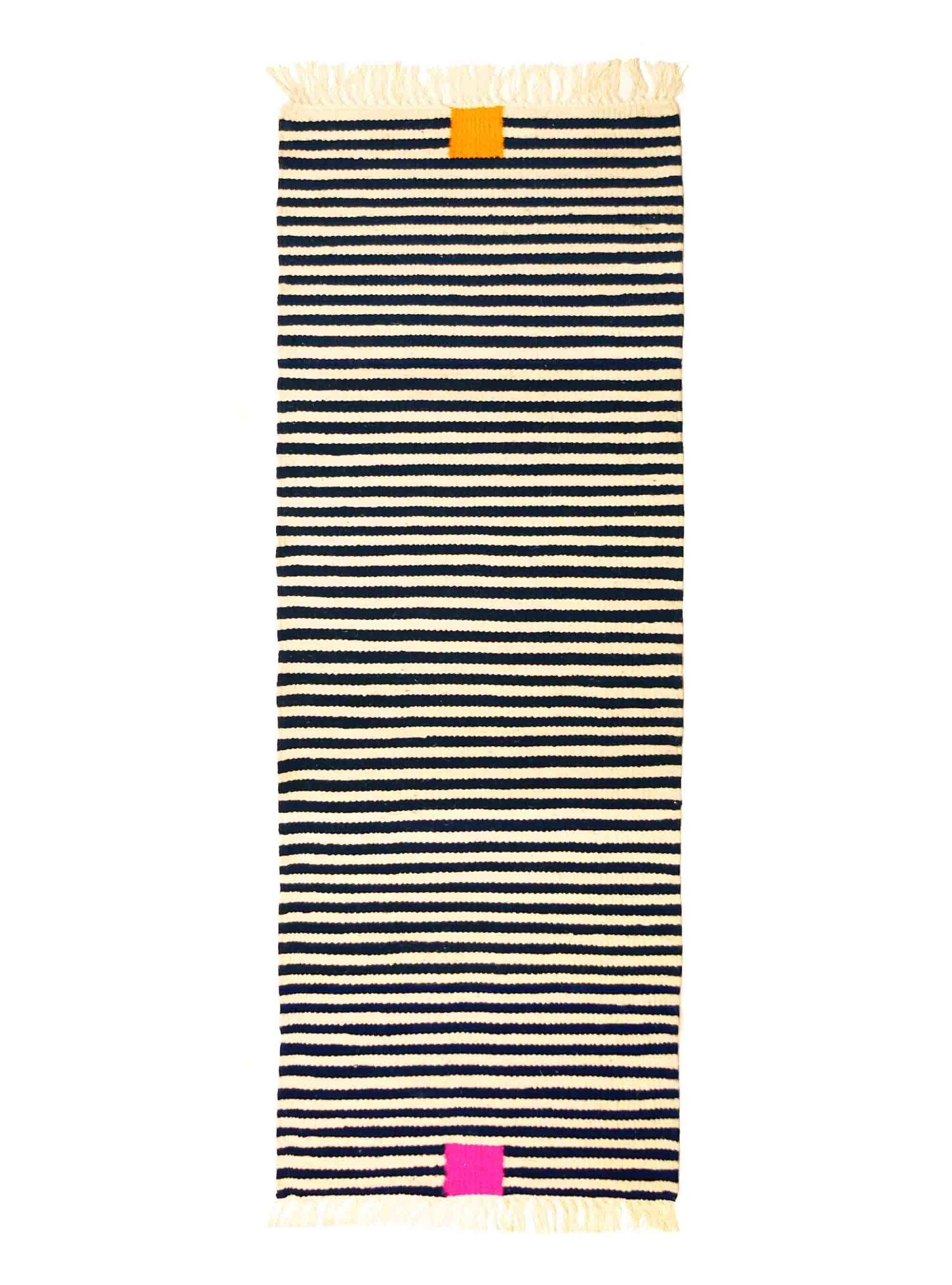 Runnerrug kira-cph Kitten-stripes no. 1 - 2.350 DKK	315 €  OUT OF STOCK – NEW ARRIVAL SPRING 15 Handwoven runnerrug made from thick lambswool and designed by kira-cph.com. The size:  70×220 cm. The runner is woven in 1,5 cm stripes in black and offwhite wool and with a dark pink and an orange square. Kira-cph.com cooperates with a  women's cooperative in North Africa, skilled women are weaving  wool runnerrugs / blankets /  bedspreads and cushions. Woven in thick, soft sheep's wool.