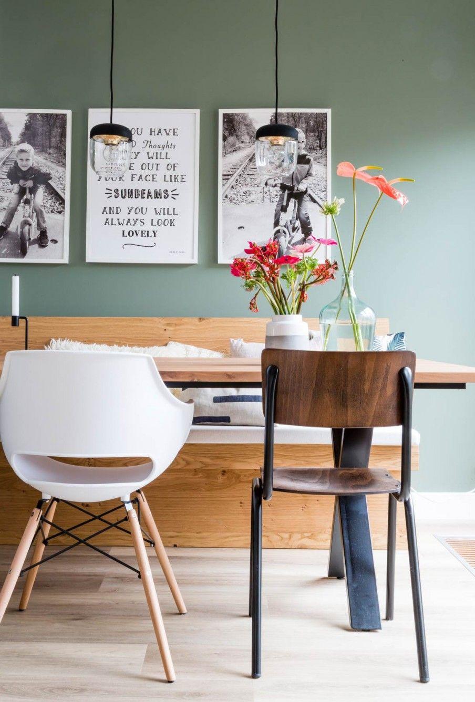 De eettafel met groene muur en schilderijen bij Jolanda en