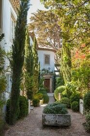 Richard Shapiro's Malibu wonder: The massive antique French front door and a circular turret are the focal point of the entry courtyard. Shapiro planted fully grown cypress and boxwood for maximum effect.