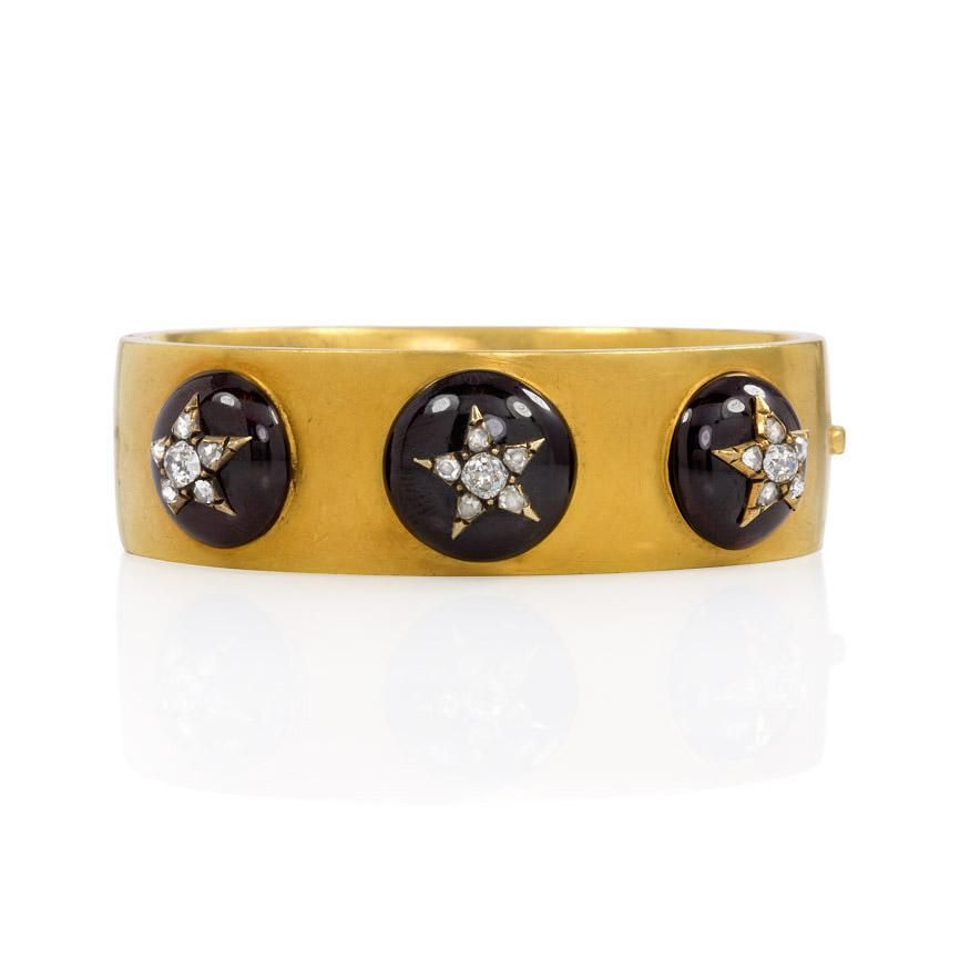 Kentshire | An antique gold cuff bracelet with three cabochon garnets set with diamond stars, in 18k. England | New York