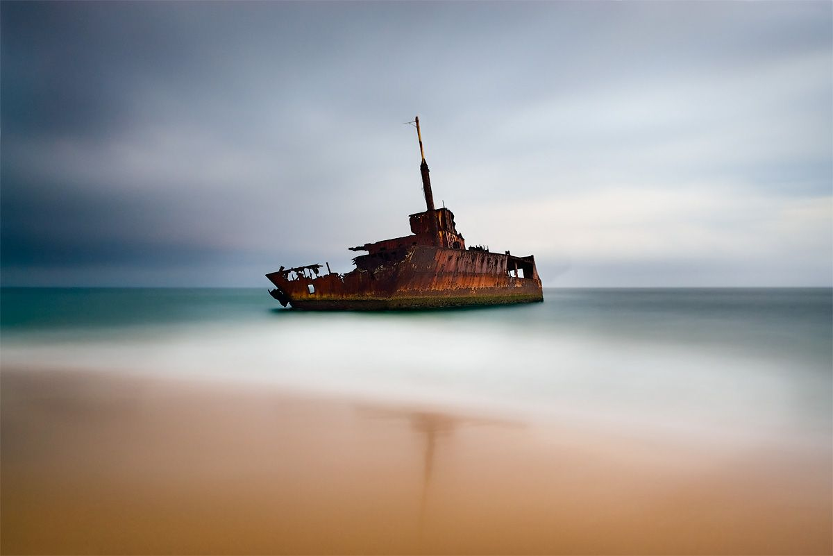 A long abandoned ship, resting alone on the sands, gazing out over the ocean where it longs to roam once again.