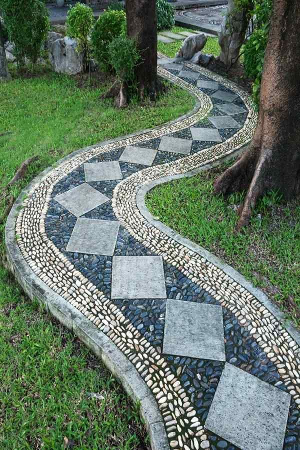 A Curving Pathway With Diamond Pavers Filled With Blue And White Stones Is  Making Its Way Through The Trees And Is Connected With Rectangular Pavers  On The ...