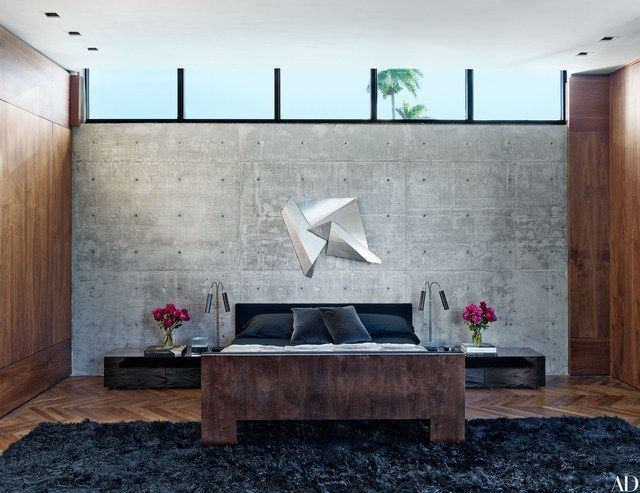 A Marsha Lega wall sculpture shines against a span of concrete in the master bedroom. Briggs Edward Solomon designed the walnut bed, which is joined by nightstands from Luminaire; the rug is by Woven Accents.
