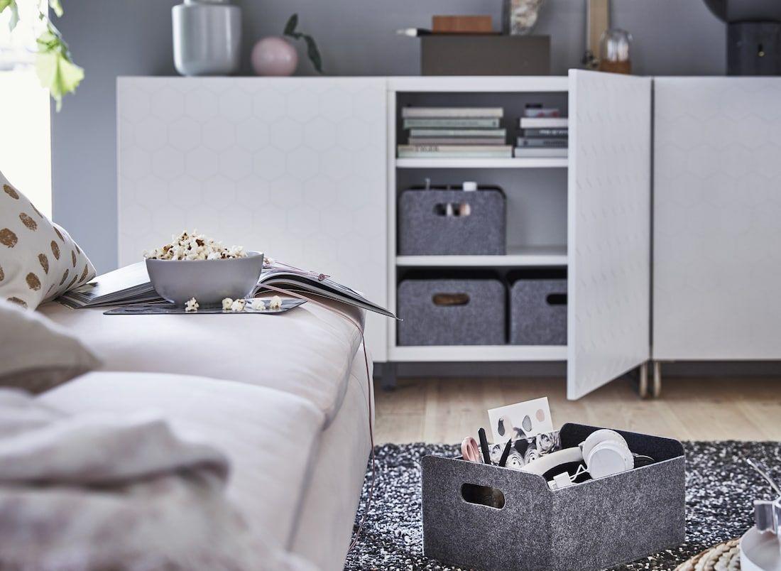 Mobile basso bianco con scatole grigie in un soggiorno ...