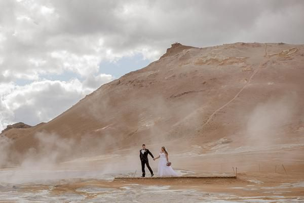 Couple walking across the Icelandic countryside for their destination wedding @myweddingdotcom