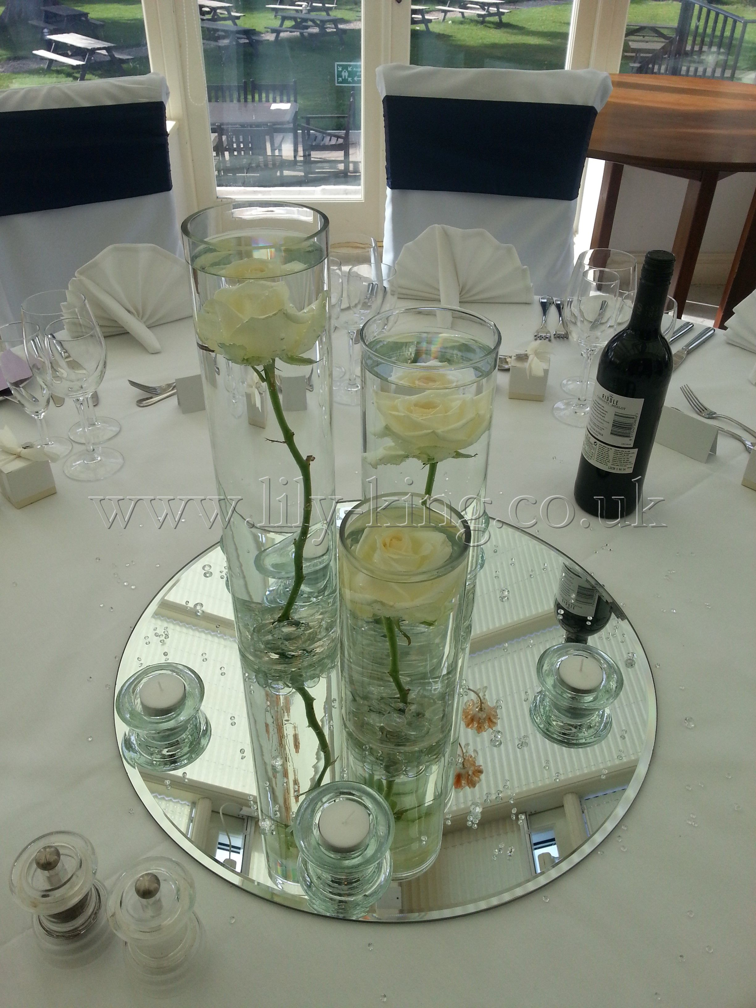 3 Cylinder Vases Of Varying Heights With A White Rose
