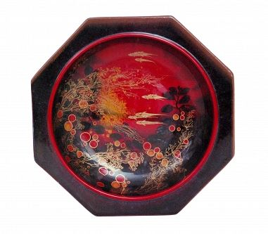 A Royal Doulton flambe octagonal Sung bowl designed by Charles Noke, the central well decorated with overlay gilt fish swimming amidst gilt reeds and grasses against a tonal red speckled glaze ground, printed marks, marked Sung, diameter 30cm