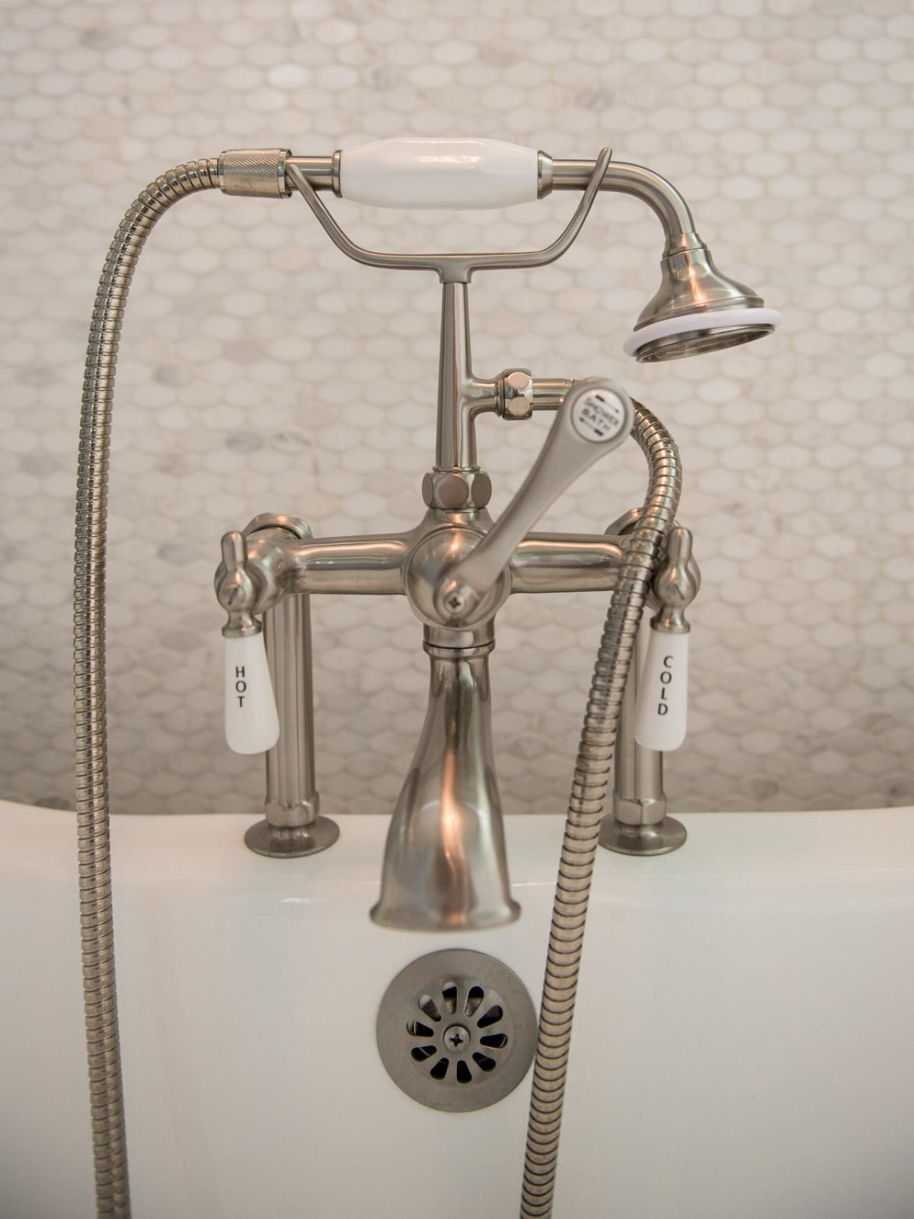 This traditional bathtub faucet also features a handheld shower ...