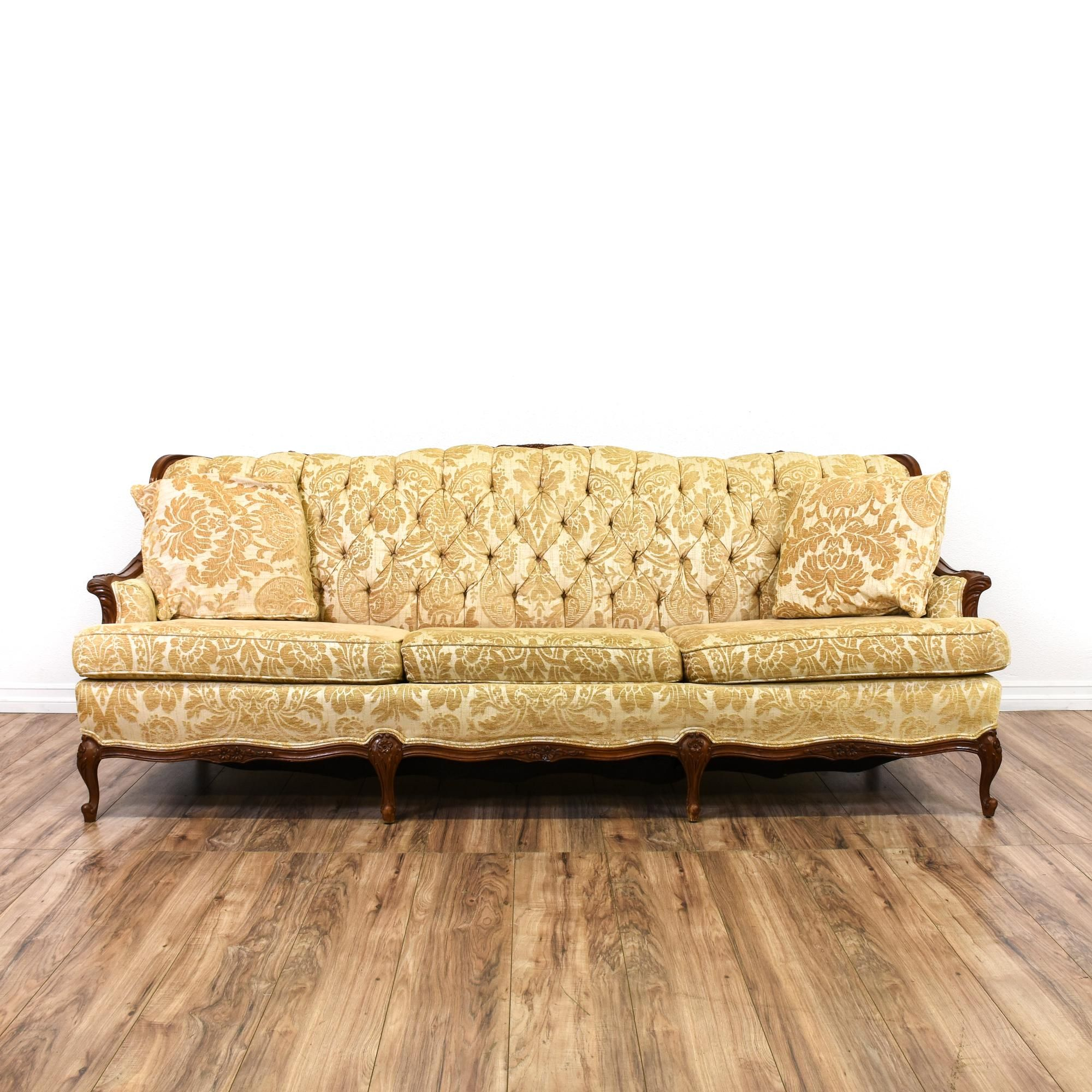 This victorian style sofa is upholstered in a durable floral damask print with beige and gold
