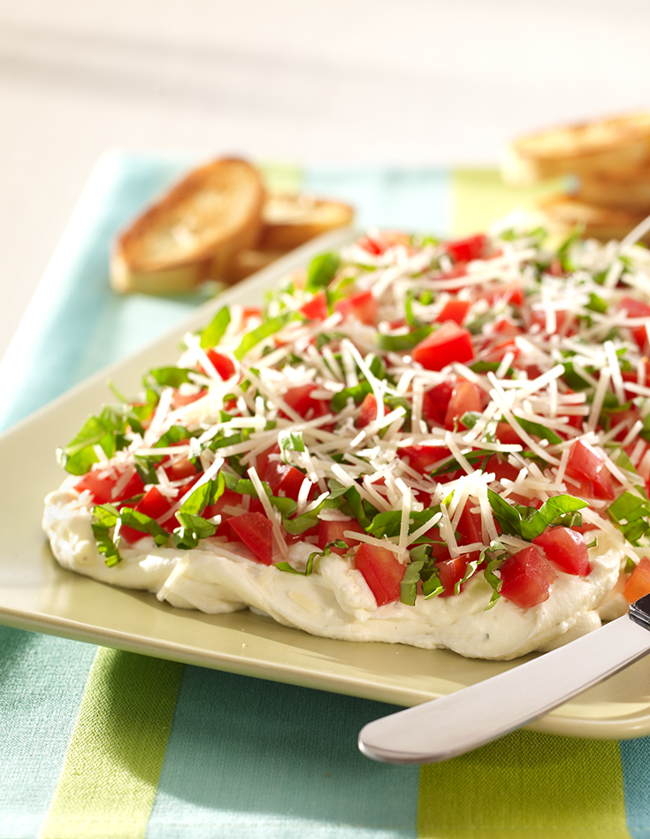 This layered spread is made with fresh basil, tomatoes, Parmesan and cream cheese. Serve with crostini for a refreshing summer appetizer.