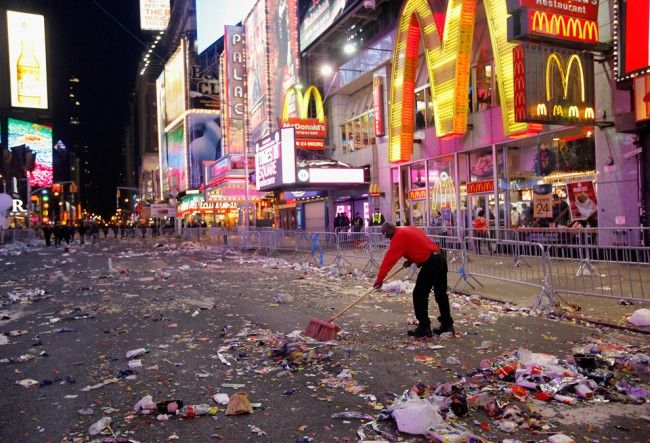 Workman begin the task of cleaning up after thousands of revelers gathered in New York's Times Square to celebrate the ball drop at the annu...