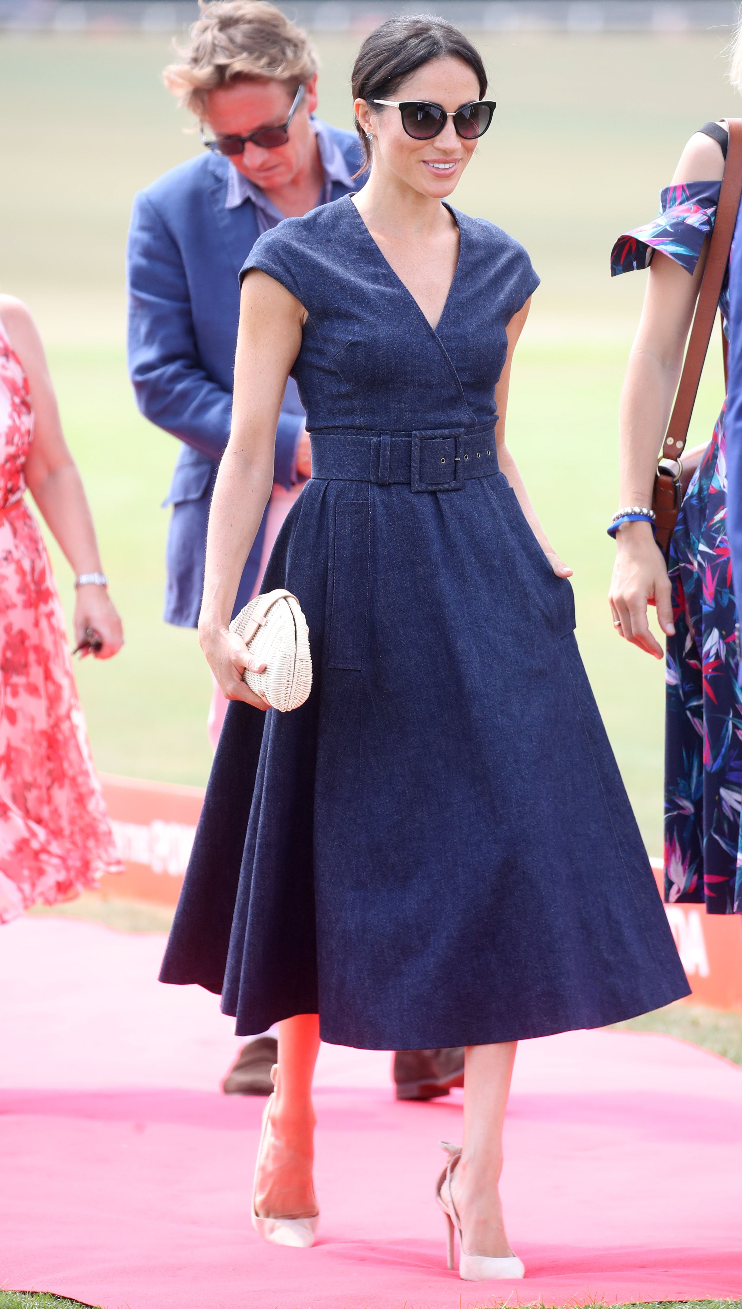 4e55cf00d7 Meghan Markle looked classy in her navy blue cotton Carolina Herrera dress  with a V neckline – Photo courtesy of Image.net   Chris Jackson   Getty  Images ...