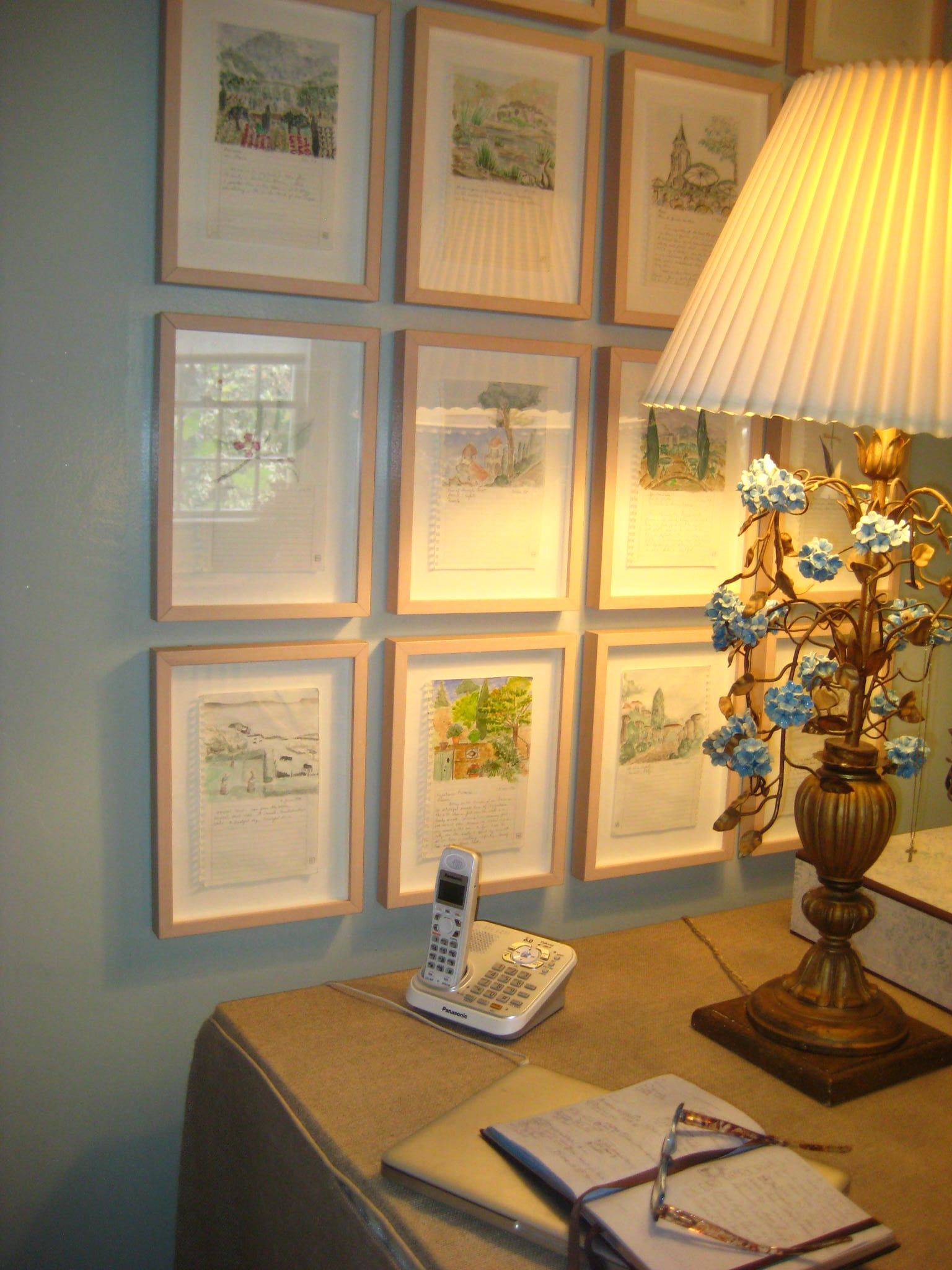 A group of framed pages from a travel sketchbook makes a charming display and forms the impression of a window. Bee Cottage, via FrancesSchultz.com