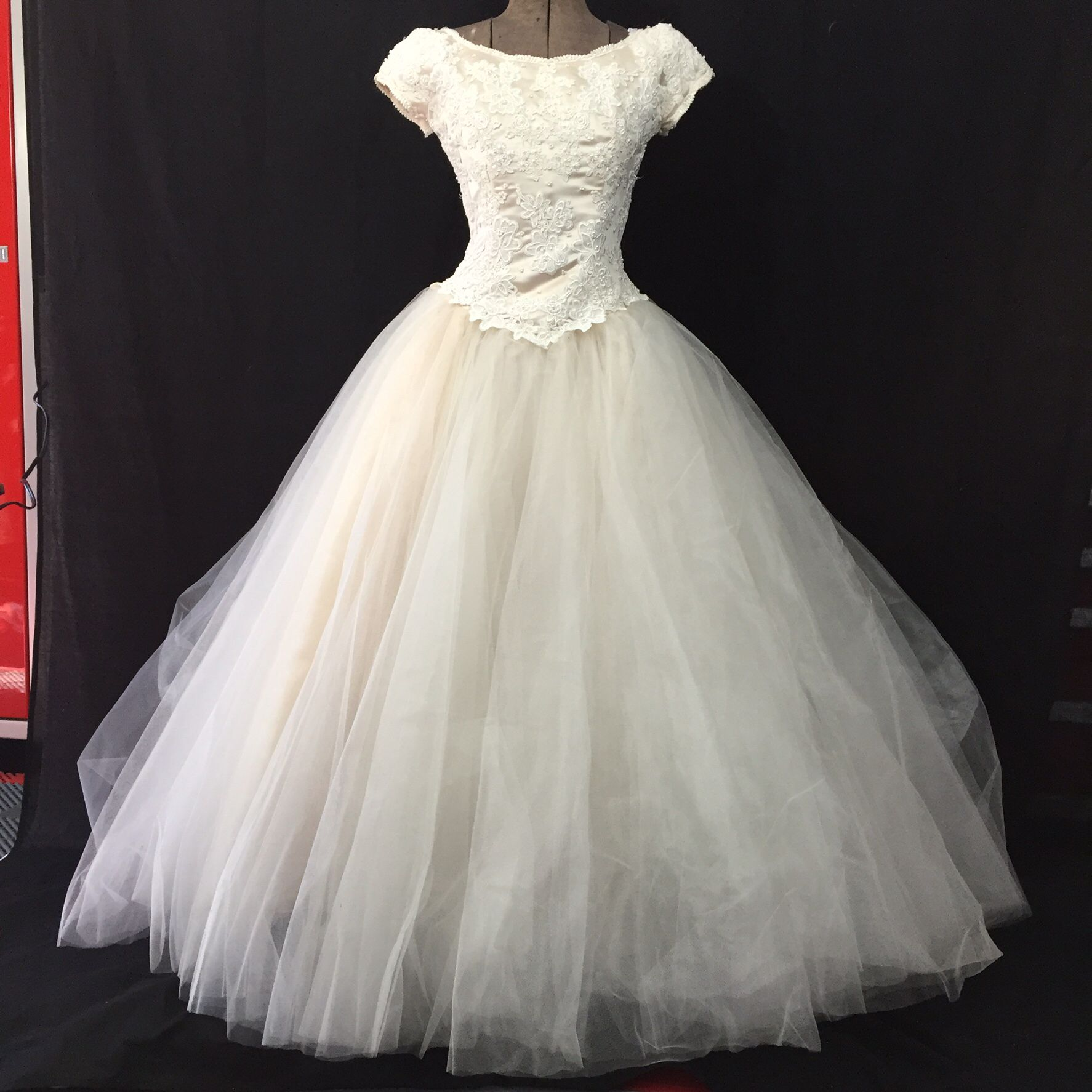 Full skirt blush colored mesh and lace. Boat neck with adorning lace .  www.blythebridalco.com