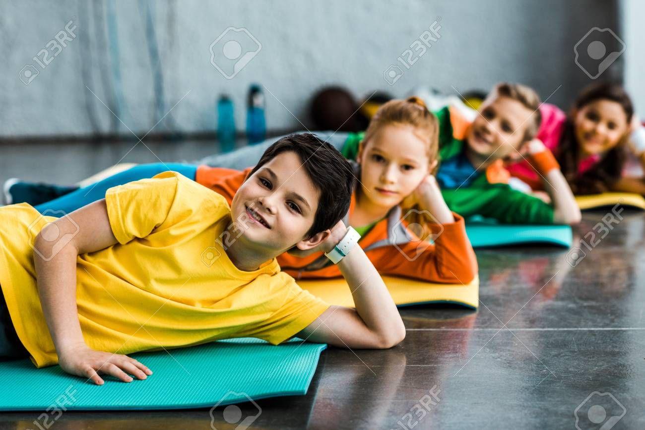 Joyful kids lying on fitness mats and looking at camera Stock Photo , #sponsored, #lying, #fitness,...